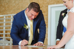 groom signing his marriage license at his wedding