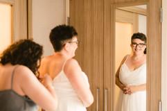 brides daughter helping her put on her wedding dress