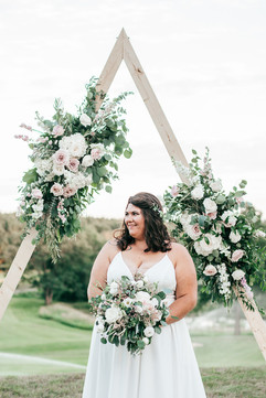 bride holding her pink, white and eucalyptus bouquet at her triangle arch wedding ceremony in michigan