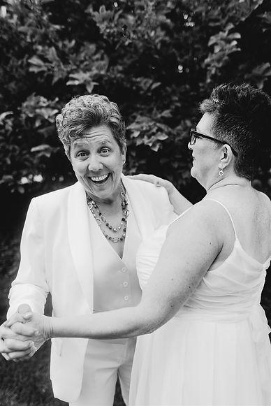 lgbtq couple smiling and dancing at their michigan wedding