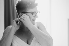 bride putting on her earings before her first look with her soon to be wife