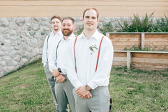 groom standing in front of a line with his groomsmen at his michigan resort wedding planned and coordinated by muse weddings based in grand raopids