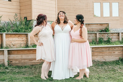 bride laughing with her bridesmaids at her wedding ceremony