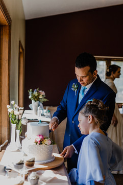 groom serving wedding cake and showing it to his daughter