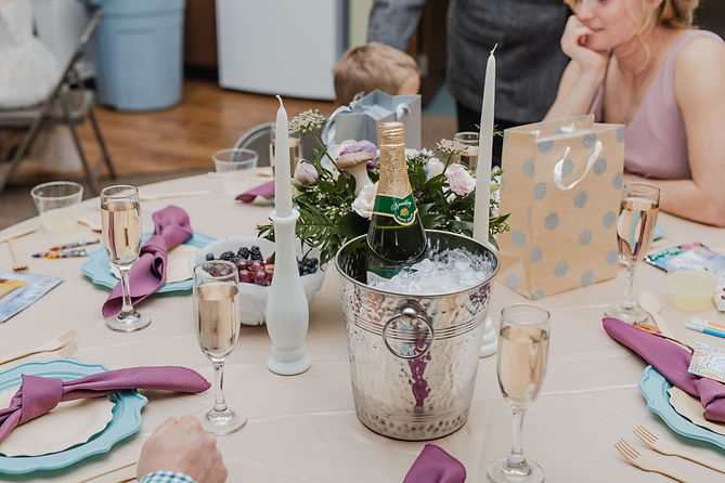 Indoor wedding reception centerpices. Tables featuring fresh berries, purple and blue colors and a bottle of bubbly. The centerpieces have mushrooms!