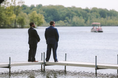groom standing on the dock waiting for his bride to enter the wedding ceremony