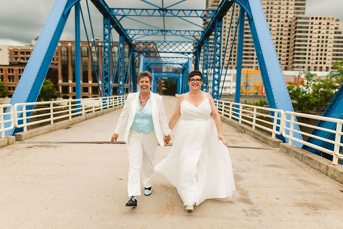 LGBTQ lesbian couple getting married and taking pictures at the blue bridge in grand rapids michigan before having their outdoor michigan wedding