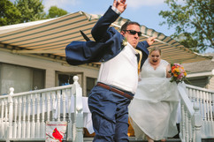 bride and groom entrance to their michigan wedding. Jumping off a patio