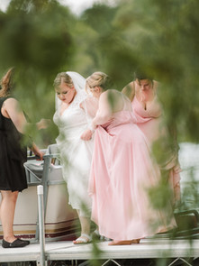 Michigan wedding planner helping bride get off a boat and enter the ceremony