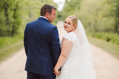 bride looking back at the camera while holding hands with her husband