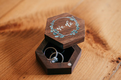 """rings being held in a wooden ring box that says """"we do"""""""