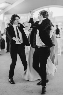 groomsmen spinning each other on ethe dance floor at a reception in millennium park in grand rapids, michigan