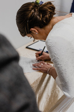 bride signing her marriage license at michigan church wedding