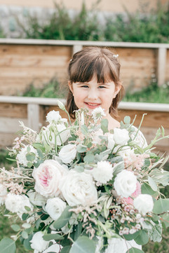 daughter and flower girl holding moms bouquet holding the brides bouquet. Absolutely adorable. Photographed by Aspen Kate Photogrphy