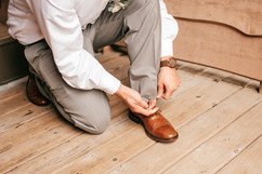 groom tying his shoes. Grey suit with brown shoes for wedding