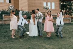 goofy photo of couple and their entire wedding party as they kiss