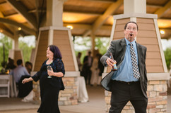 officiant and brides best friend playing cornhole at an outdoor wedding