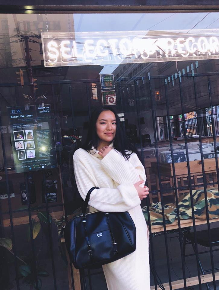 Katy Ho posing in front of a glass window