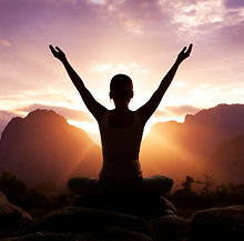 woman meditating with hands held high and open in front of a sunrise