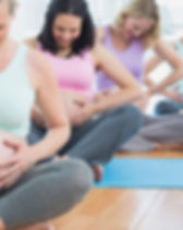 Pregnant women sitting on mats touching