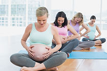 Pregnant women sitting on mats touching