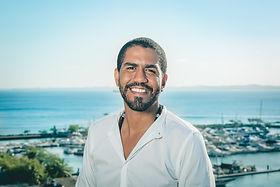 """Amós Heber é ator (Bacharel em Artes Cênicas/UFBA), roteirista, escritor e cantor. Como roteirista concorreu em 2018 ao NETLABTV como finalista na categoria de ficção com o seu projeto de série dramática """"Alma Faminta"""", participou do III Laboratório de Narrativas Negras promovido pela FLUP/RJ e a Rede Globo em 2019 e compôs a sala de roteiro da série """"Condomínio"""" da produtora Cavalo do Cão (PRODAV). Participou da Formação de Roteiristas para Narrativas Seriadas """"Usina do Drama"""" (FACOM/UFBA) Como escritor lançou em 2015 o livro """"Furúnculos"""" e foi contemplado com a Bolsa de Criação Literária da FBN/DLLLB, com o projeto """"Sinal Fechado"""". Ganhou o 3º lugar no Concurso Literário do Servidor Público Estadual – Bahia em 2014, e participa das coletâneas nas edições de 2014 e 2015. Está na plataforma digital """"Mapa da Palavra"""" e na revista """"Cartografias"""" da FUNCEB/BA. Participa da coletânea soteropolitanos (2020). Integrou o projeto """"Grafias Eletrônicas"""" em 2017 e participou das edições da FLICA 2016 e FLIGÊ 2017. No audiovisual participou como ator dos longas """"Tungstênio"""" de Heitor Dhalia e """"Receba"""" de Rodrigo Luna e Pedro Perazzo. Participou das séries de TV: """"O Pequeno Gigante"""" da LartyMark/Cinearts, """"Os Sonhadores"""" da Obá Cacauê"""", """"Juacas"""" da Disney Channel, """"Frequência Positiva"""" da 3Tabelas e """"Balaclava"""" da Movioca. Também apresentou o programa """"Diversidades"""" da TV IAT/BA."""