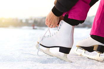 woman-tying-ice-skates-laces-by-a-lake-o