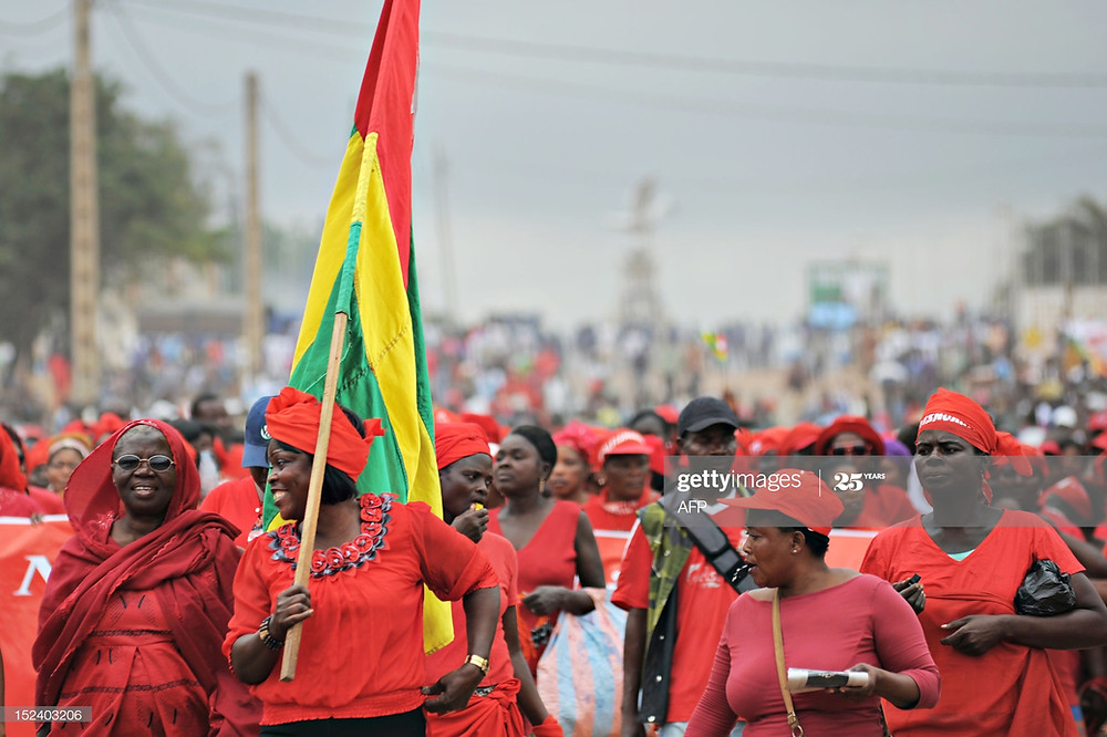 Togo's Eliane Amegah (2nd L) holds a Togolese national flag on September 20, 2012 in Lome as she joins several thousand women dressed in red to march in the capital in the latest string of protests by a group demanding sweeping political reform. Men and youths joined the march organised by the women's wing of Let's Save Togo, an opposition and civil society coalition that has called on Togo's President Faure Gnassingbe to resign. AFP PHOTO / Daniel Hayduk (Photo credit should read Daniel Hayduk/AFP/GettyImages