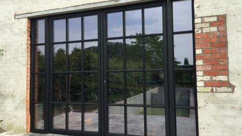 Mooi en slank steellook raam SL38 van Reynaers Aluminium in Ral-kleur 9005 Coatex structuurlak. Referentie te Sint-Niklaas.