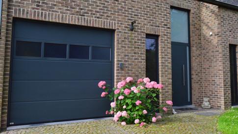 Sectionale garagepoort Hörmann voorzien van beglazing het bovenste paneel.