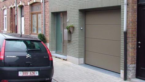 Mooie sectionale garagepoort van het merk Hörmann, gecombineerd met een stijlvolle aluminium voordeur van het merk Reynaers aluminium.