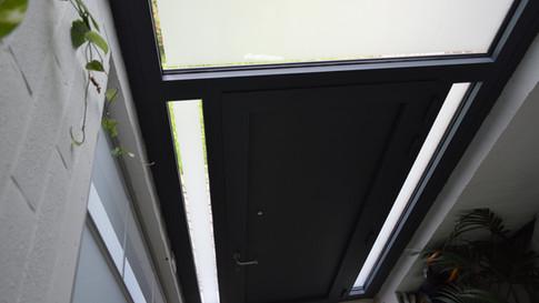 Aluminium ramen, deuren en erker van het merk Reynaers. Gecombineerd met een poort van het merk Hörmann. Met zorg geplaatst te Haasdonk (Beveren). (Foto 8)