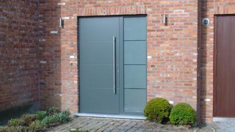 VINCK aluminium voordeur met vleugel-overlappend paneel, geplaatst te Sint-Niklaas. Zijlicht met gezandstraald glas met horizontale heldere lijnen.