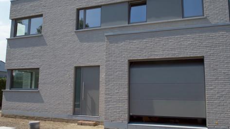 Reynaers ramen en deuren in nieuwbouw woning te Belsele, gecombineerd met onze comfortabele Hörmann sectionale garagepoorten.