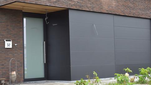 Combinatie van inkomdeur + secionale garagepoort + aluminium plaatwerk die 1 mooi totaal vormen te Zele. (Foto 1)