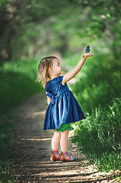 Girl in blue dress in the park by the river catching butterflies for a children session in Saskatoon SK