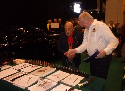 Sir Stirling Moss O.B.E. examines the finalists' submissions.
