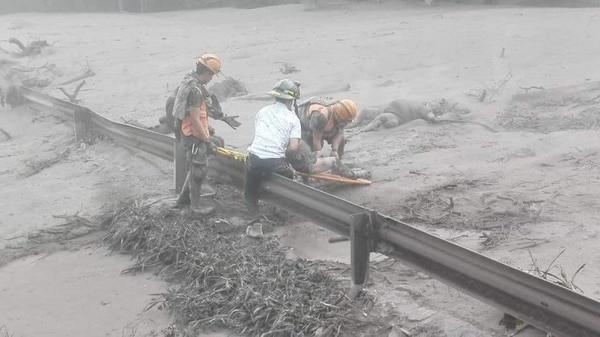 Fotografía, cedida por el Ministerio de Defensa de Guatemala, que muestra a personal de emergencia rescatando a una persona después de la erupción del Volcán de Fuego registrada hoy en Guatemala (EFE/ Ministerio de Defensa Guatemala)