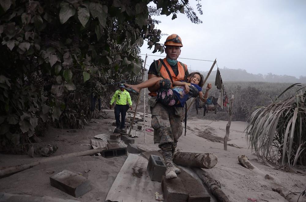 Un miembro de los equipos de rescate ayuda a una niña en El Rodeo. EFE/NOE PÉREZ
