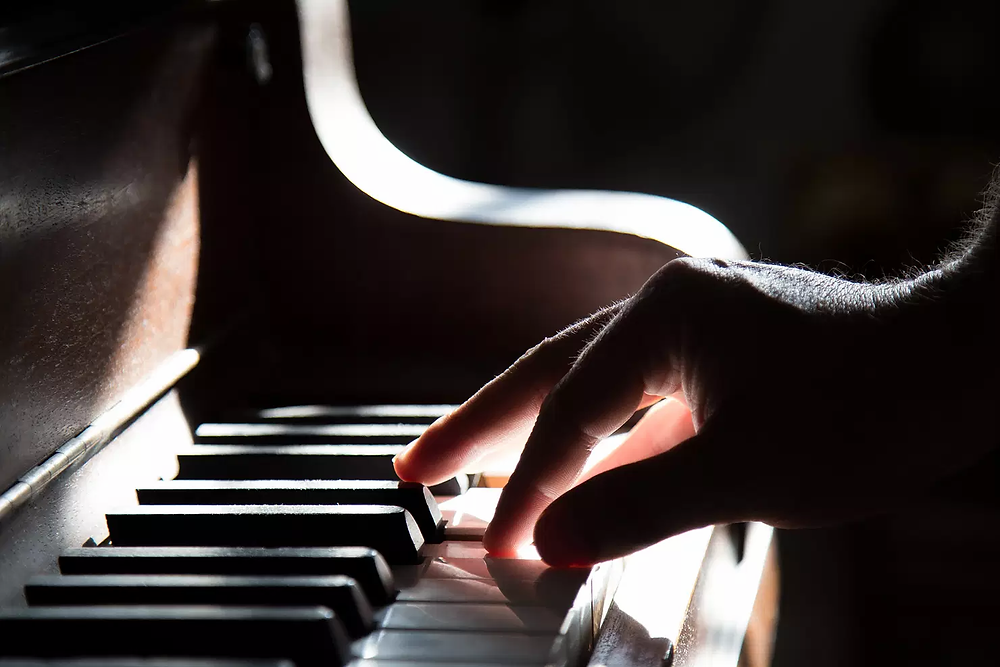 A photo by Tadas Mikuckis, showing a hand playing the piano