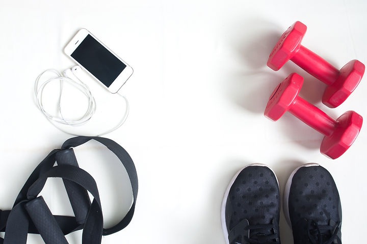 Flat lay of cellphone, red dumbbells and