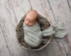 newborn baby boy in rustic wrap on wood backdrop