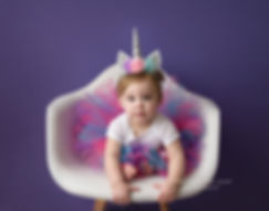 baby in unicorn and tutu sitting in white chair with purple background first birthday photography