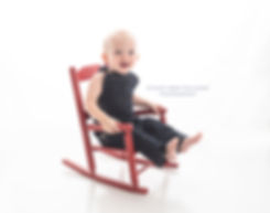little baby boy in overalls on red rocking chair with white background