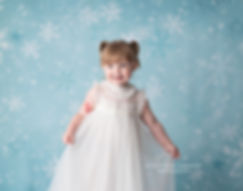 child photography of little girl in white trish schully dress, against blue frozen snowflake ice backdrop