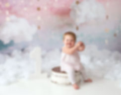 happy baby clapping hands first birthday photography pink white clouds