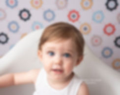 portrait of blue eyed baby girl in white chair