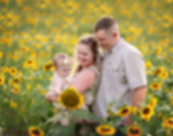 baby with parents in sunflower field at milford family farm in cumming georgia