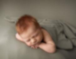 redhead newborn boy on sage green backdrop