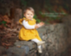 baby girl sitting on stone wall professional child photography in roswell georgia
